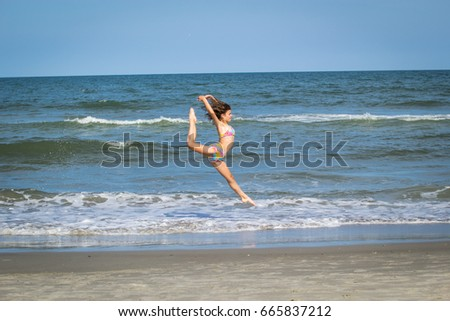 Young adolescent girl dancer on the beach leaping in the air