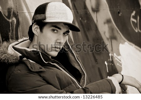 Young adolescent in casual clothing over grafted wall - stock photo