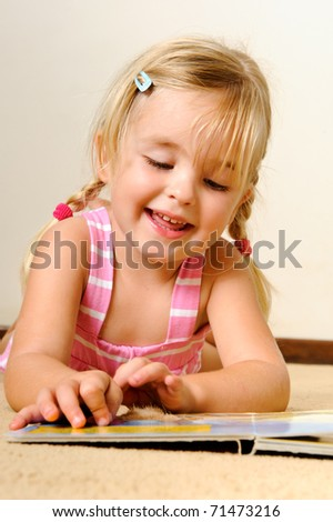 young adorable blonde girl reads a book on her own