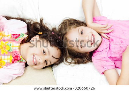 Young adorable hispanic sisters lying down playing and embracing each other happily while smiling to the camera, shot from above angle. - stock photo
