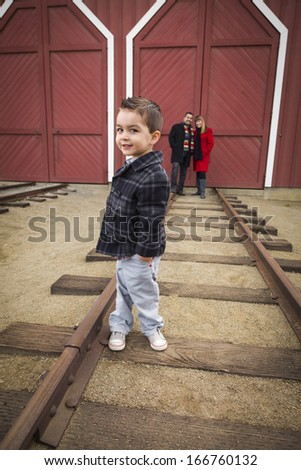 Young Adorable Mixed Race Boy at Train Depot with Parents Smiling Behind. - stock photo