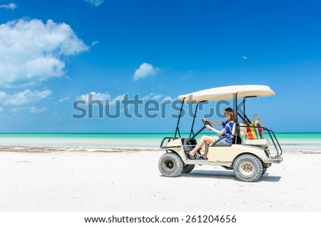 Young adorable woman driving on a golf cart along tropical white sandy beach during her Caribbean vacation on Holbox island, Mexico - stock photo