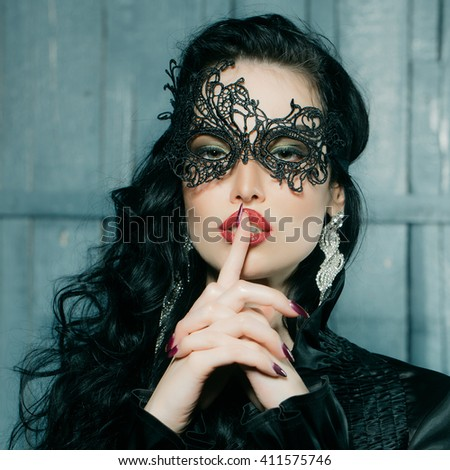 Young adorable woman with sexy face and red lips wearing black party mask with diamond earrings