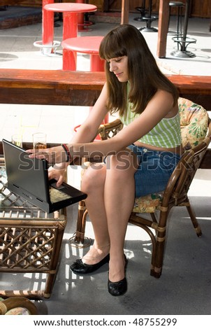 Young adul girl in bar with drink and laptop