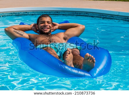 Young adult african-american male lying on raft having fun in swimming pool during summer. - stock photo