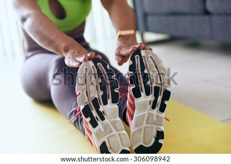 Young adult african american woman in sports clothing at home, doing domestic fitness and training on yellow pad. The girl does muscular legs stretching touching feet with hands - stock photo