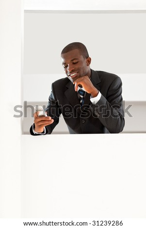 young adult afro-american businessman reading emails on his smartphone indoors. Copy space - stock photo