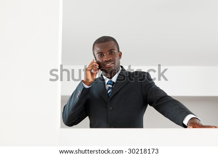young adult afro-american businessman talking on the phone indoors. Copy space - stock photo