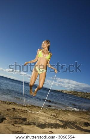 Young adult Asian Filipino female in bikini jumping rope on beach in Maui Hawaii. - stock photo