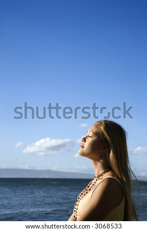 Young adult Asian Filipino female standing on beach in Maui Hawaii. - stock photo