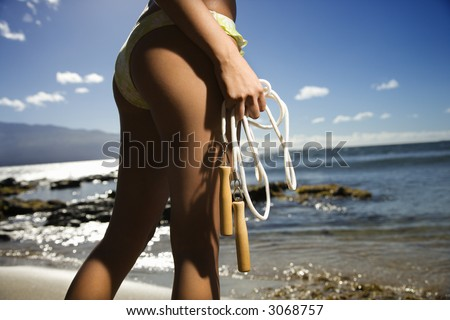 Young adult Asian Filipino female standing on beach in swimsuit holding jump rope Close up of buttocks of Asian Filipino young adult female holding jump rope in swimsuit on beach in Maui Hawaii. - stock photo