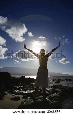 Young adult Asian Filipino female stretching arms in air on beach in Maui Hawaii. - stock photo