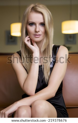 Young adult attractive and sensuality blonde woman in black elegance fashionable dress sitting on the couch - stock photo