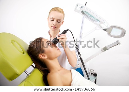 Young adult attractive brunette woman receiving laser therapy. Spa studio shot