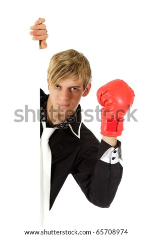Young adult, attractive caucasian man behind wall wearing red boxing glove. Copy space. Studio shot. White background.