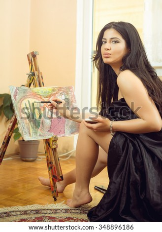 Young adult attractive girl painting artistic image on canvas in apartment - stock photo