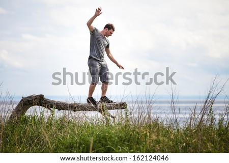 Young Adult Balancing on a dead Tree in Nature. - stock photo