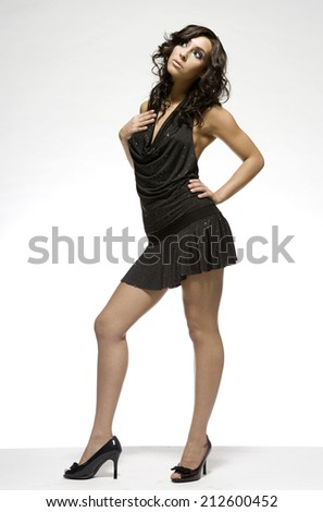 Young adult beautiful brunette wearing black dress on light background