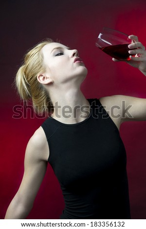 young adult blond girl wearing black underwear having red wine  - stock photo
