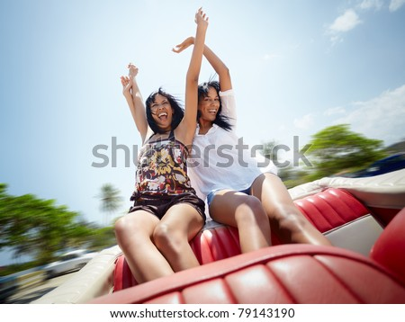 young adult brunette twin women sitting in convertible red car and laughing. Horizontal shape, front view, copy space - stock photo