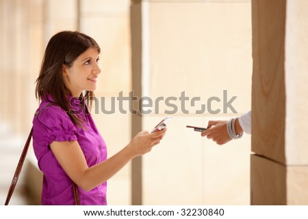 young adult businesswoman exchanging data with colleague's mobile phone via wireless technology. Copy space - stock photo
