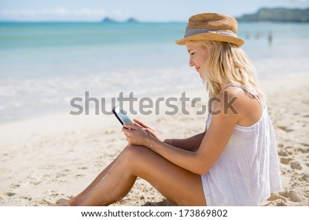 Young adult caucasian blond business woman on beach vacation using tablet pc computer - stock photo