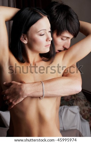 Young adult Caucasian couple in passionate embrace during sexual foreplay