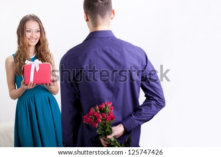 young adult couple giving presents to each other