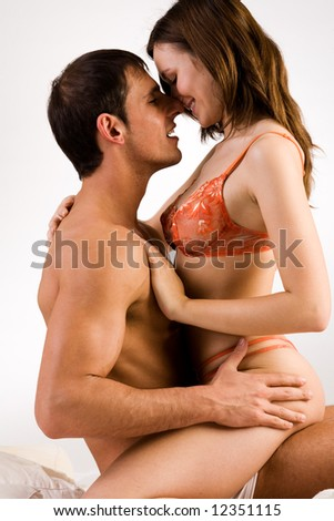 Young adult couple in the studio on a bed - stock photo