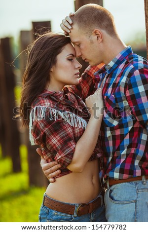 young adult couple on the farm standing near fence, man in the foreground - stock photo