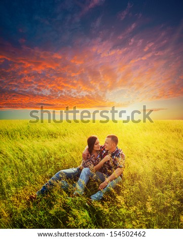 young adult couple sitting in the field over sunset - stock photo