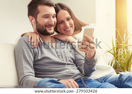 young adult couple sitting on sofa and listening to music together, looking at phone and smiling - stock photo