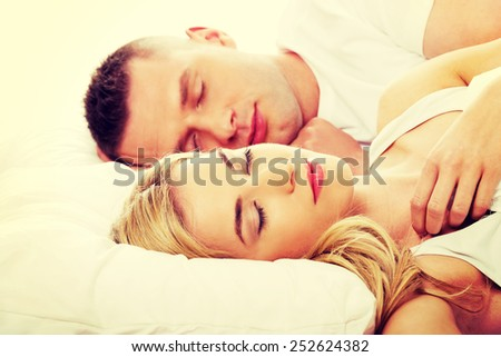 Young adult couple sleeping on the bed in bedroom - stock photo