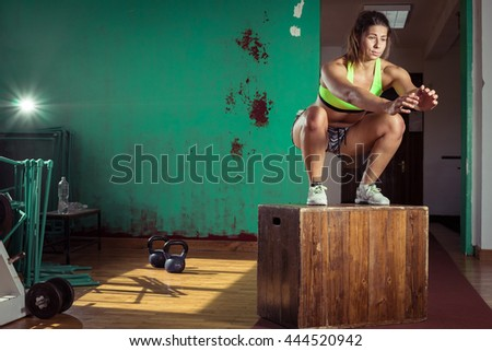 Young adult crossfit girl jumping on box in gym club.