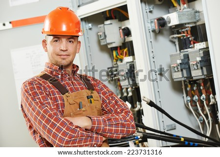 young adult electrician builder engineer worker in front of fuse switch board - stock photo