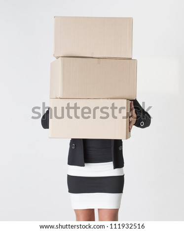 Young adult female carry a stack of boxes during a move from one office to another - stock photo