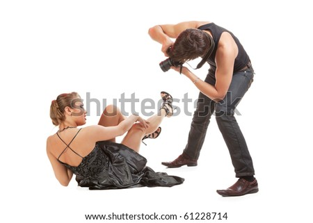 Young adult female Caucasian model being photographed in studio by young  male photographer. - stock photo