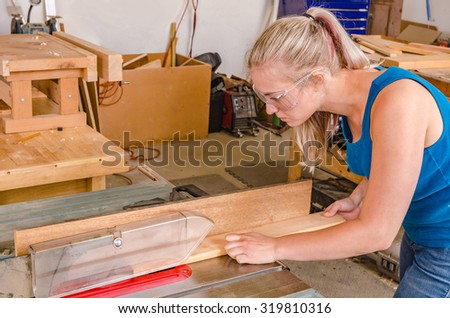 Young adult female Caucasian woodworker ripping board on table saw in workshop - stock photo
