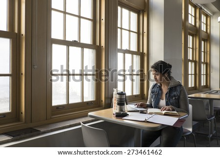 Young adult female hispanic studying, reading, researching information - stock photo