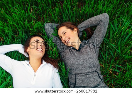 Young Adult Females friends laying in grass laughing and smiling - stock photo