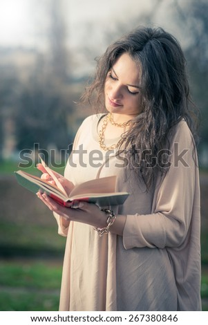Young adult girl reading a book in park wearing nice blouse - stock photo