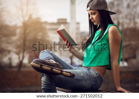 Young adult girl sitting in park on bench and reading a book. - stock photo