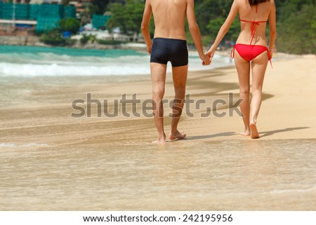 young adult happy couple in sunglasses on the beach, back view - stock photo