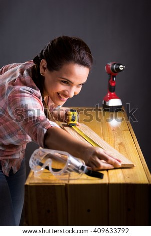 Young adult Hispanic woman measuring a wooden board with a tape measure - stock photo