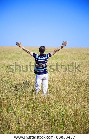 young adult is in the field raskinv hand in hand, rear view - stock photo