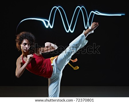 young adult latin american female doing capoeira side kick in gym, with streaks of led lights on top. Vertical shape, full length, front view, copy space - stock photo