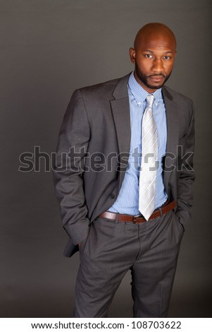Young adult lifestyle shot of a black businessman dressed in a suit with his hands in his pockets looking confidently into the camera with a shaved head on a grey background - stock photo