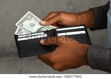 Young adult making a payment.  Broke. Teenager needing money. - stock photo