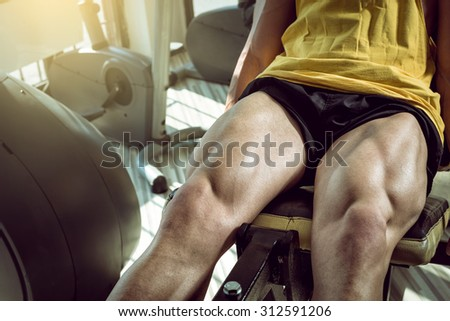Young adult man doing leg extension workout exercise in gym