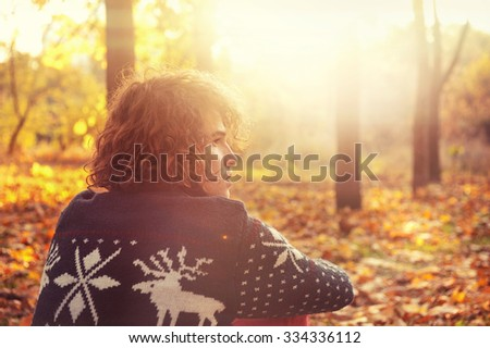 Young adult man dressed in knit sweater with deers sitting on autumn leaves in a sunset park, backlight outdoor - stock photo